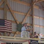 Auctioneer spitting numbers as the bids come in for pigs in the ring at the Marquette county Fair 2015